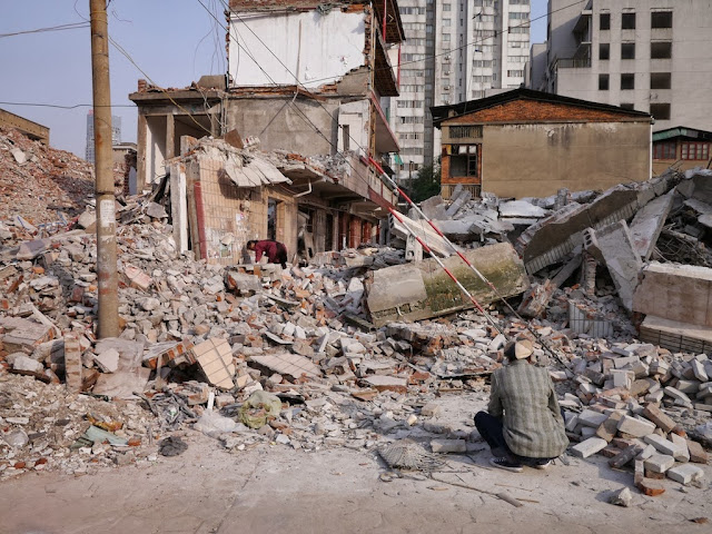 man squatting down in front of demolished buildings at Beizheng Street in Changsha