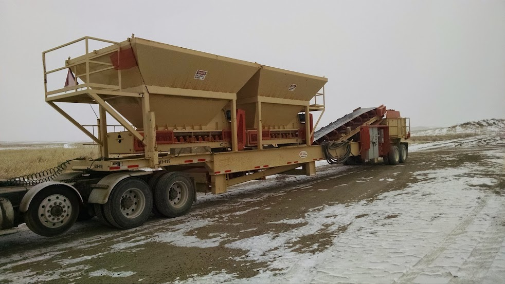 large industrial hoppers loaded on flatbed trailer