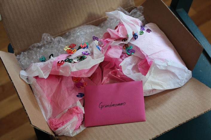 cardboard box full of pink tissue paper and confetti