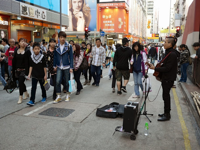 young man singing and playing guitar at Sai Yeung Choi Street South