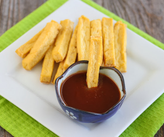a bowl of dipping sauce with a baked tofu fry in it and more fries on the plate