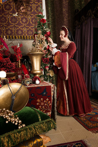 Costumed performer portraying Mairi de Guise adds the final flourishes to the Christmas tree