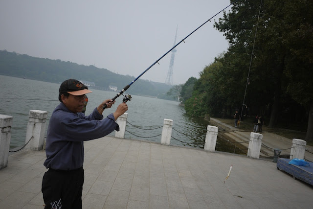man wearing a baseball cap and holding a fishing rod in Changsha, China