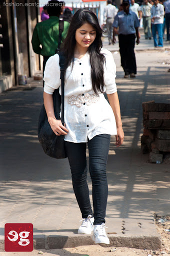 Cool white top with a belt, jeans, comfortable shoes and a bag for a sunny day.