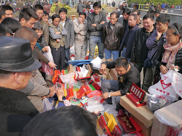 crowd surrounding a seller at an outdoor antique market in Changsha, China