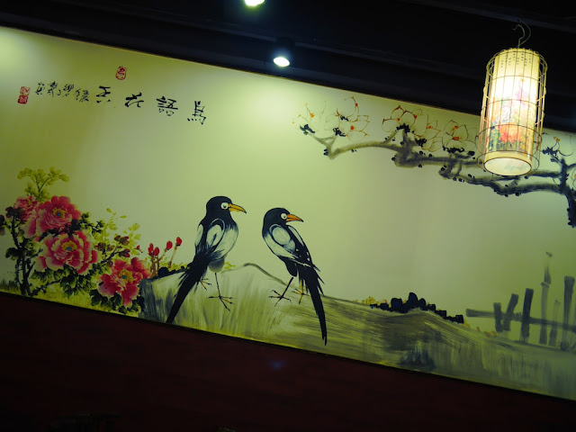 A wall at a restaurant in Hengyang with a classical Chinese style painting of a scene with two birds.