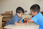 Children in Montessori preschool can always choose to work alone, or with a chosen playmate. These boys are working together with the Binomial Cube, a puzzle that concretizes the mathematical formula (a+b)^2.