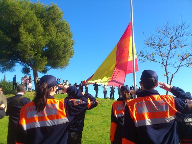 Voluntarios de Protección Civil rindiendo honores a la Bandera.