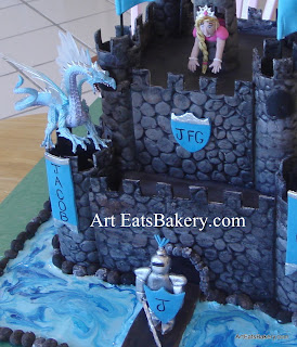 Creative boy's castle birthday cake design with edible knight, princess and flags. The dragon is the boy's toy. clos