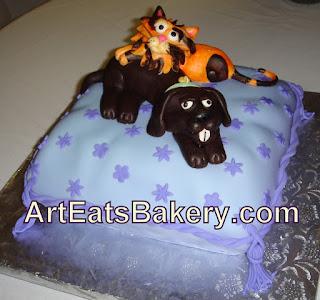 Fondant and chocolate cat and dog sculpture on pillow cake. http://www.arteatsbakery.com Art Eats Bakery Greenville,SC