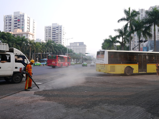 a bus and truck going around a man using a blower to move gravel and creating a large dust cloud on a street in Zhuhai