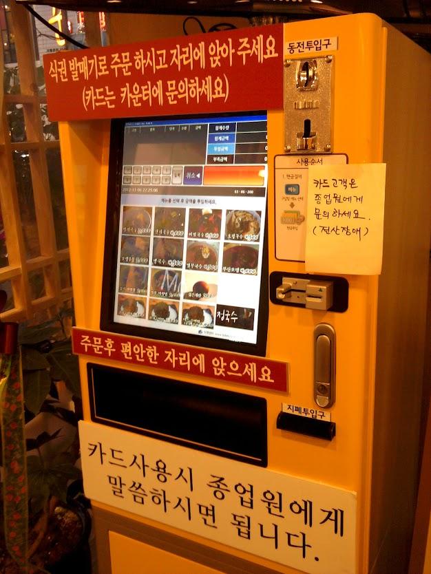 Viduje pasitinka geltonas automatas su begale neaiškaus teksto ir maisto paveiksliukais