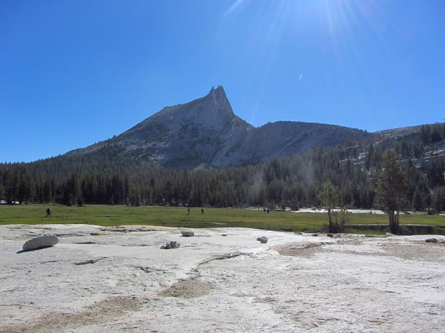 backpackers crossing the meadow below Cathedral Peak