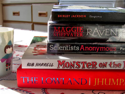 Pile of books: Hangsman by Shirley Jackson, The Raven Boys by Maggie Stiefvater, Scientists Anonymous by Patricia Fara, Monsters on the Hill by Robert Harrell, The Lowland by Jhumpa Lahiri