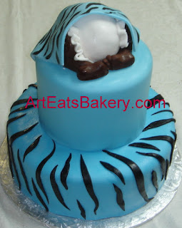 Blue and black zebra stripped two tier custom designed baby boy shower cake with baby under a blanket