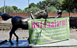 Banner: »Hafenalarm!« an einer Skulptur befestigt.