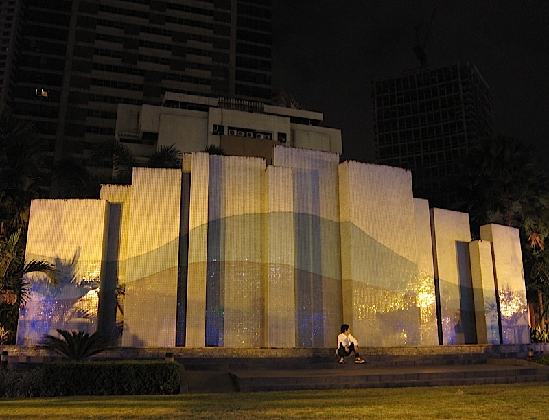 young man in front of the hill-patterned wall at the Ortigas Park