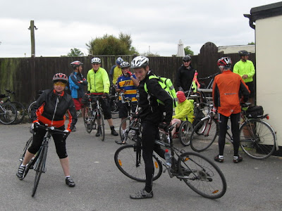 Large group of cyclists outside cafe