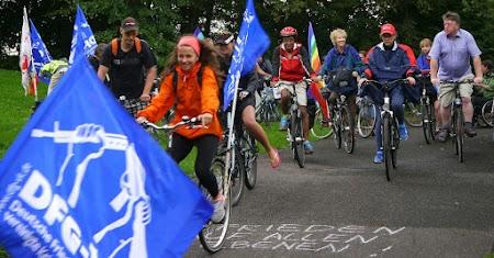 Radfahrerinnen mit blauen DFG-VK-Fahnen.