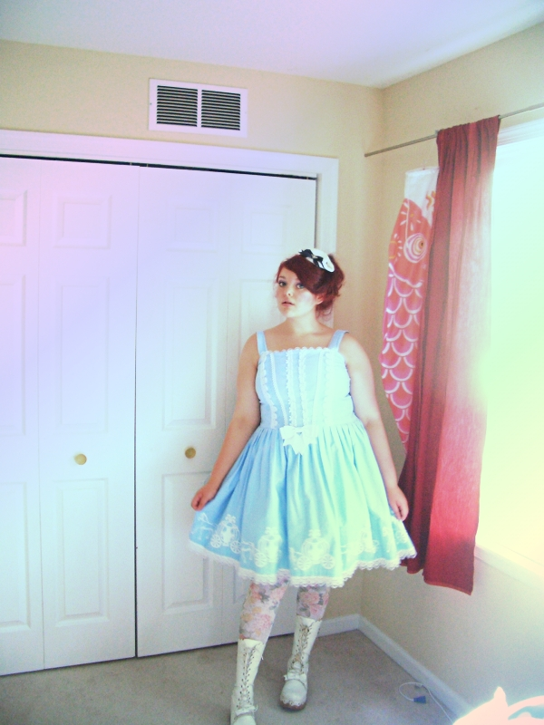 Img: a pale, fat, red-haired, young woman in a light-blue, sundress-style dress adorned with white lace and Cinderella screenprint. The skirt of the dress puffs out from the waist. On her legs are floral tights and white cork-platform boots. On top of her head is a miniature white tricorn hat. She is standing against a white door next to a window and sunlight is streaming into the room.