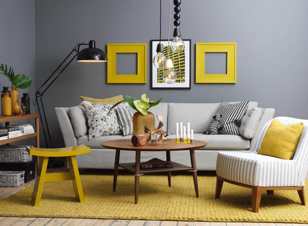 A Combination Of Gray Wall With Light Sofa Accented Shades Yellow Such As Picture Frames Stool Throw Pillow An Area Rug And Other