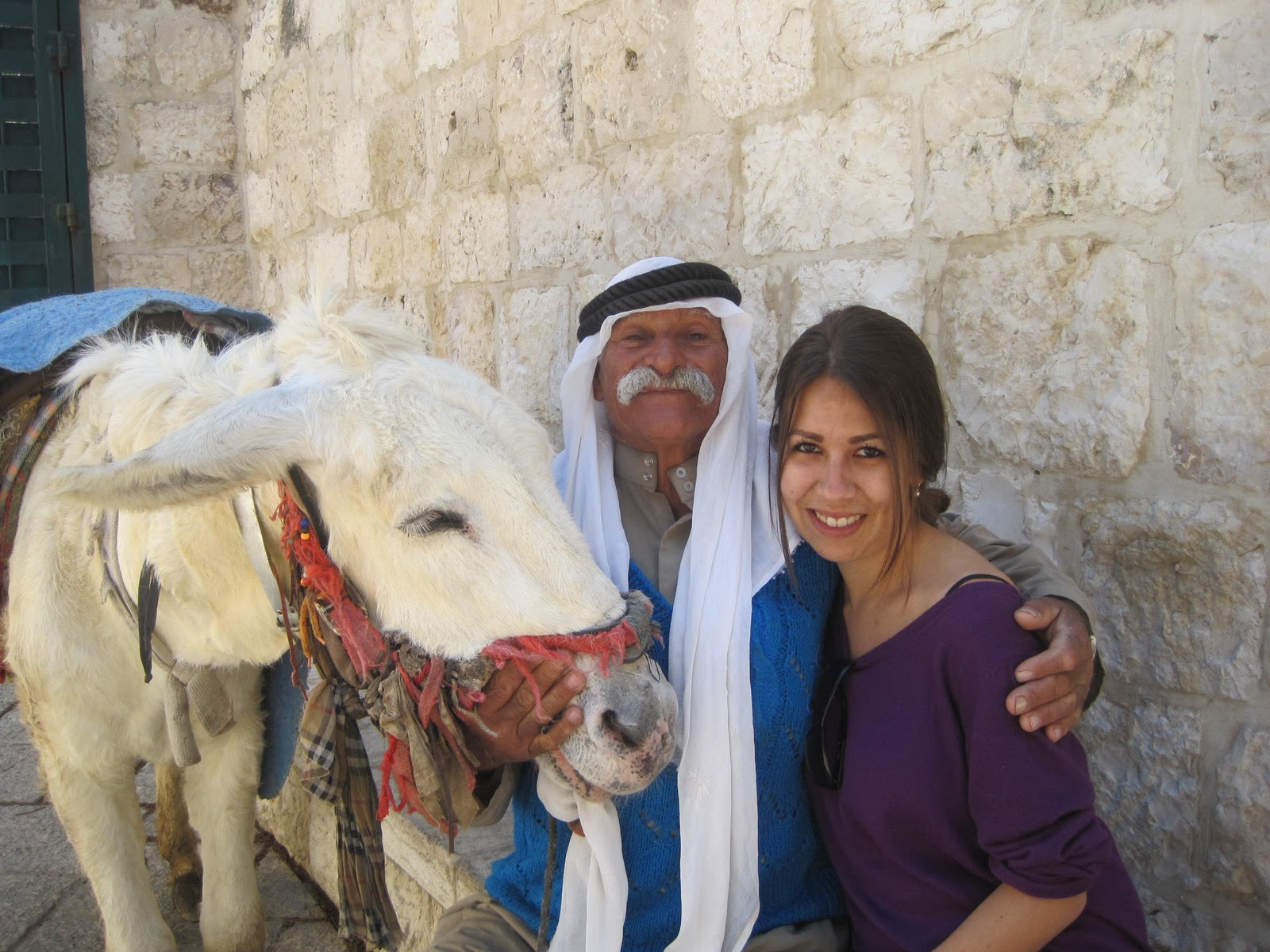 Sister with donkey sitting outside of the Jewish cemetery.