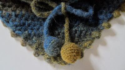 Close up of  tan through to blue Wrap crochet scarf pompoms.