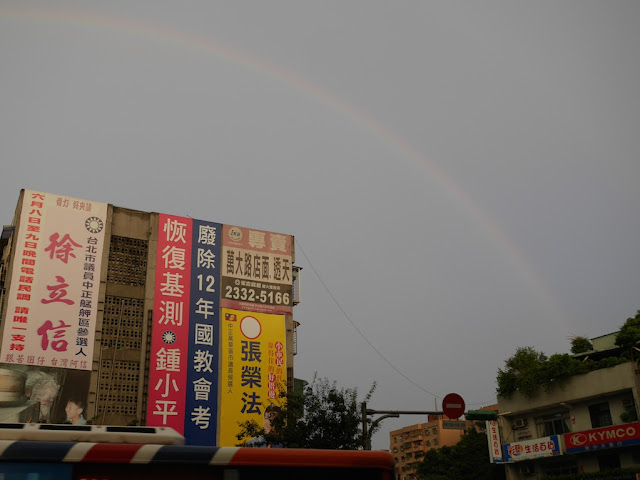 rainbow arching over buildings in Taipei