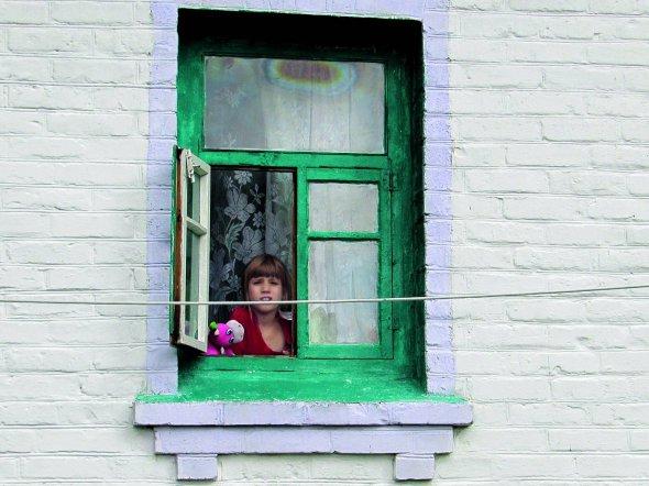 Першокласниця Марія Фень дивиться звікна свого будинку. Приїхала збатьками доЦіпків із-під Попасної Луганської області