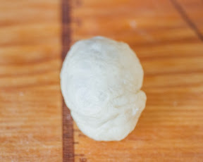 process photo showing the egg wrapped in the dough