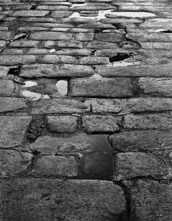 Piso em pedras de granito muito irregulares no tamanho com alguns charcos de água