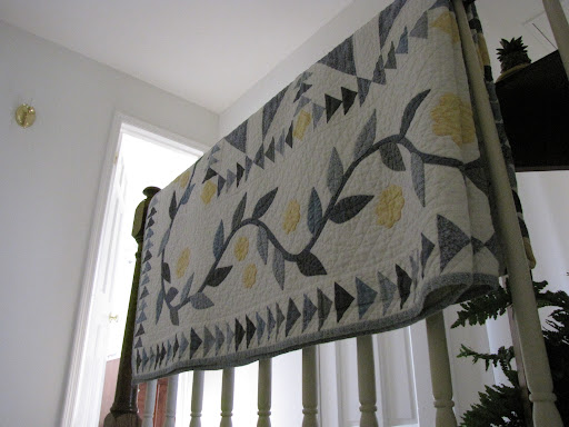A quilt drapes the banister in the stairway - of course. Like in most houses.