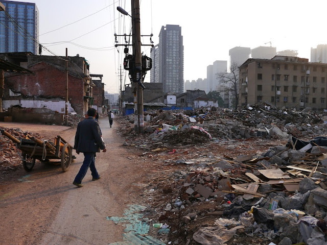 man with a two-wheeled wooden wheelbarrow collecting scraps from the demolished buildings at Beizheng Street in Changsha