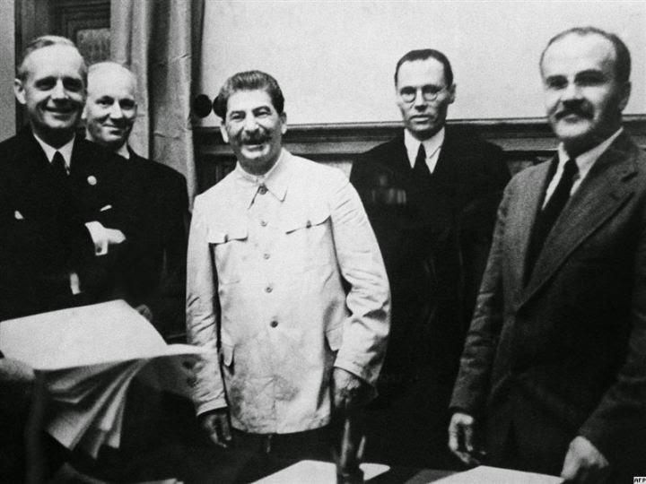 O Ministro do Exterior da Alemanha, Joachim Von Ribbentrop (de braços cruzados), o líder soviético, Josef Stalin (de branco), e o Ministro do Exterior da URSS, Vyacheslav Molotov (extrema direita), após a ratificação do Tratado Molotov-Ribbentrop em 23 de agosto de 1939. Fotografia: autor desconhecido.
