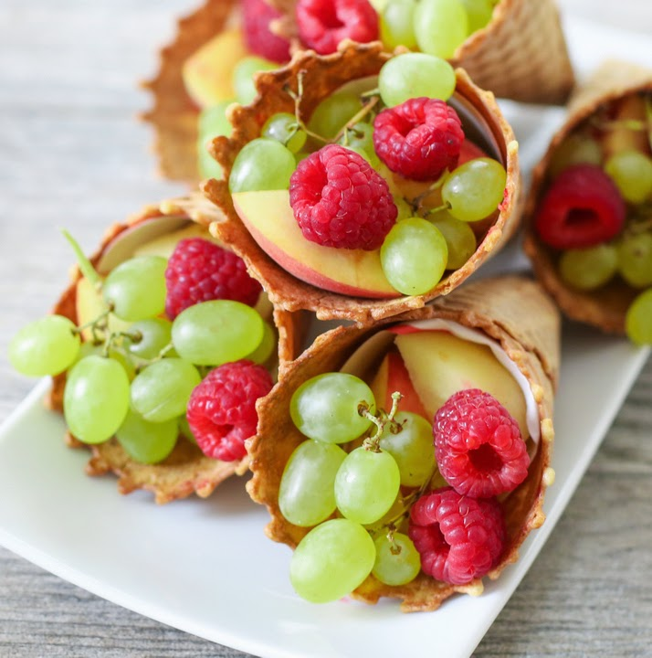 a close-up photo of fruit cones on a white serving dish