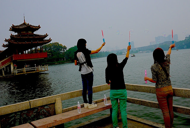 young women making bubbles at a park in Changsha, China