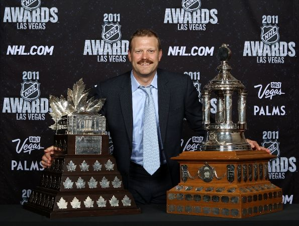 Tim Thomas posing with the Vezina Trophy and the Conn Smythe Trophy