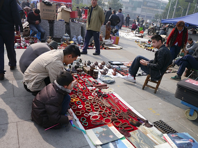 man and boy looking at items at an outdoor antique market in Changsha, China