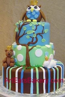 Three tier blue, green and brown stripes and polka dots baby shower cake with tree, owl, teddy bear and bunny