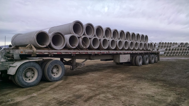 large 4-axle flatbed loaded with cement sewer pipe