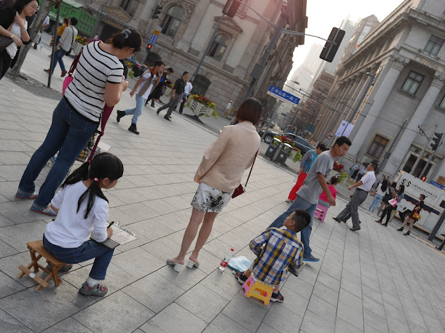 girl and boy drawing buildings at The Bund in Shanghai