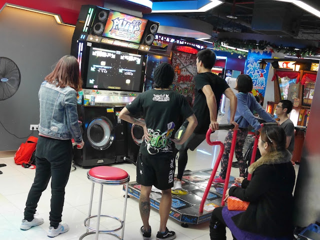 people playing a dance video game in D-Mall in Shanghai