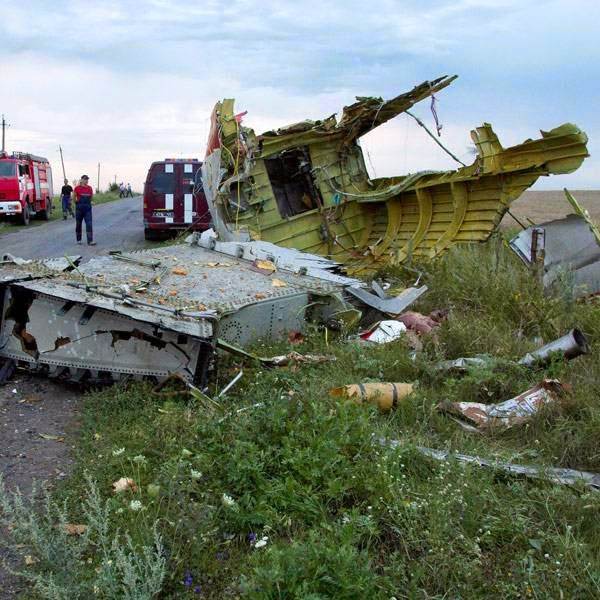 Ukrainian rescuers walk past debris at the crash site of a passenger plane near the village of Grabovo, Ukraine, Thursday, July 17, 2014.