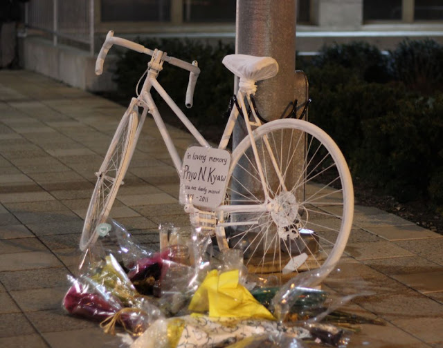 a bicycle painted all white and chained to a lamppost, with a sign on it giving the biker's name and dates, and a pile of flowers and candles in the foreground