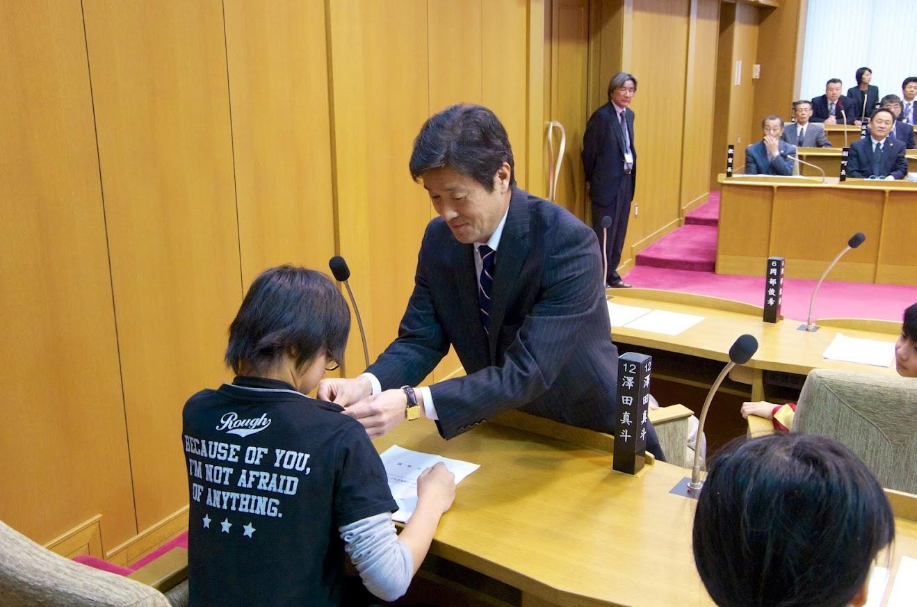 議員バッチを付ける佐々木康弘 議長