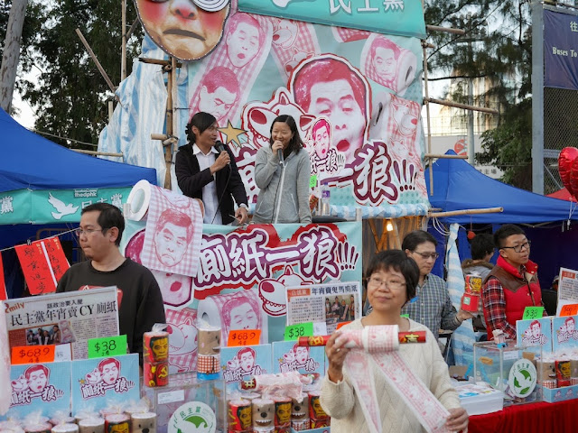 Woman displaying toilet paper with Hong Kong Chief Executive Leung Chun-ying's face