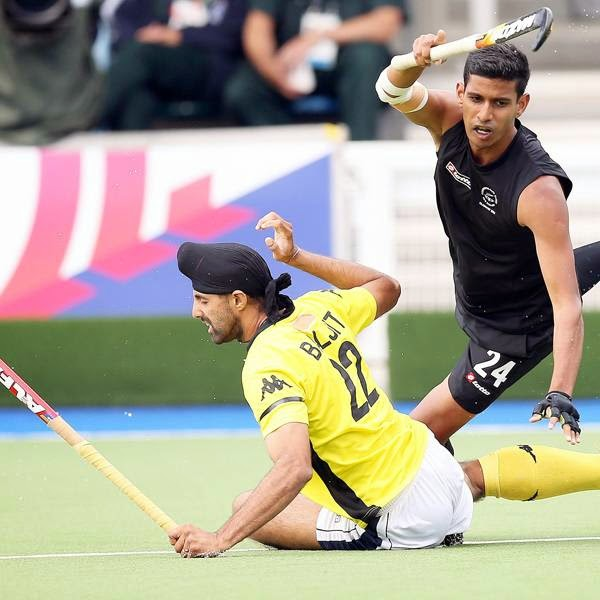 New Zealand's Arun Panchia, right, vies for the ball with Mayalsia's Singh Bajiit Charun Singh, left, during their men's field hockey match at the Commonwealth Games Glasgow 2014, at the National Hockey Centre, in Glasgow, on July 31, 2014.