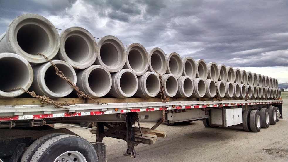 flatbed trailer loaded with cement pipes