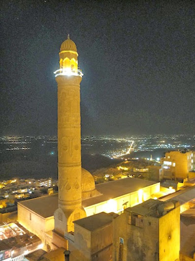 Minaret amb les ciutats il·luminades al fons