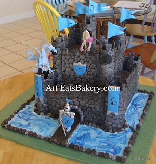 Creative boy's castle birthday cake design with edible knight, princess and flags. The dragon is the boy's toy